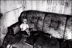 A torn up old doll with a missing leg sits on a sofa in a filthy abandoned house.