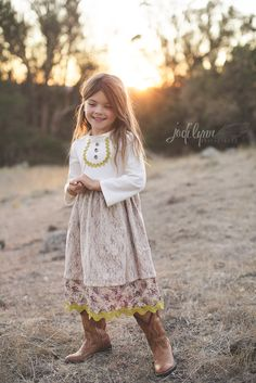 Perfect for the Country Fair, a trip to the rodeo, or a day running through the prairie grass, this dress has it all!  The cream knit top dress is comfy and inviting for Fall weather, and boasts a charming double-layer skirt in a tiny wildflower print and cream lace. Chartreuse Ric Rac lines th...