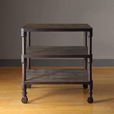 Get more storage space with this functional three-tiered shelf wood end table with storage. In a cool grey color with caster wheels for ease of movement, this 26-inch-tall end table allows items to be displayed neatly on individual shelves.
