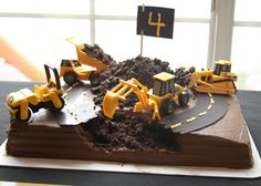 Construction Cake! Chocolate cake, chocolate frosting, sugar paper road with yellow frosting, and crumbled up chocolate wafers or Oreos