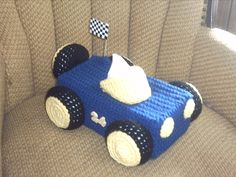 Race Car tissue box cover.  you can have your favorite NASCAR drivers number put on the sides and made in his colors.  there is a spare tire on the back with a checkered flag on the side.  this fits over the short-long box.  it has a drawstring on the bottom for easy insertion of a new box.  this is made with royal blue yellow and black yarn.  this sells for l0.00 and can be ordered by emailing me at train5021@yaho #car #cars #tissueboxcovers #crochet #nascar
