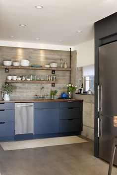 kitchen with open shelves made from 100-year-old floor joists; board formed concrete wall.