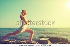 young woman  doing yoga on  coast of  sea on  beach - stock photo