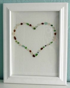 Rachel of One Pretty Thing hot glues Sea Glass onto canvas. The result, an artful Sea Glass Heart.