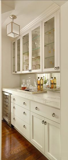 Beautiful bar / buffet idea. With quartz counter to mimic the kitchen. Wrong color though. Love the glass cabinets. Very clean look.