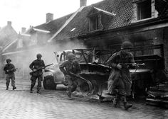 American paratroopers of the 101st Airborne Division march past a destroyed truck in Veghel. #WW2