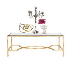 Choose thismetallic gold, glass-topped coffee table, which will exudeelegance and style for your modern contemporary home. The candle stand adds height and statuesque glamour andiscomplemented byanantique silver votive, to help shake the monotony that symmetry can sometimes bring. Add an elaborate tea-light holder to bring the eye back to the surface. A bowl ofpotpourri adds a dash of colourand complements the metallics well. Read our blog to shop these products!