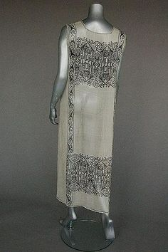 A Mariano Fortuny stencilled white gauze tabard, (back view) early 20th century, printed with Near Eastern motifs of black scrolls and edging lines, side slits.
