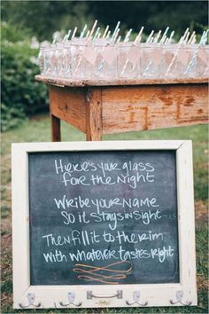 """Drink Station with a sign that reads """" Here is your glass for the night. Write you name on it so it stays in sight. fill it to the rim with whatever tastes right"""""""