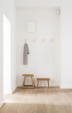 Ultra-minimalist entryway with a rustic touch in the form of two wood stools. @aesencecom