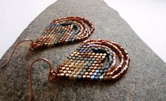Earrings by SoulLovin on Etsy. Beadwoven brick stitch earrings,  triangle shaped with an arrow pattern within the triangles, and dangling loops of beads