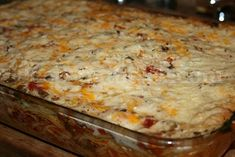 BAKED SPAGHETTI by TRISHA YEARWOOD - A perfect potluck casserole, this one feeds a crowd! Using a basic tomato based spaghetti meat sauce as a base with layer of spaghetti noodles & cheese, finished with a cream soup topping