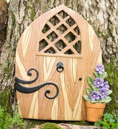"Miniature Fairy Garden Scroll Door Tree Accent: Hang our Miniature Scroll Door and Window Set on a tree to encourage local elves and garden fairies to come and go through your yard. The Scroll Door with its scrolled ""hinges,"" handles and little window, adds a fun, fanciful touch to any fairy garden. The Windows feature tiny shutters and detailed window boxes. Beautifully painted, detailed resin fairy accents are weatherproof and durable in any season. These miniature accents are charming…"