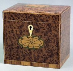 An amboyna rectangular tea caddy of George III design with slightly domed top and front inlaid with oval fan motif, 5.5ins wide x 4.25ins x 5.5ins high from The CANTERBURY AUCTION Galleries