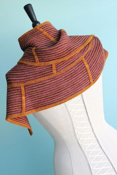 Clockwork is an enjoyable striped garter stitch shawl/scarf, perfect for featuring two beautiful colors of yarn. Bold slipped stitch columns add structural interest while increases give this gear-inspired design a unique arched shape. Picking colors is always the hardest part, but have fun and be prepared to make a striking statement.