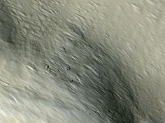 A piece of Mars: Right at the edge of the largest volcano on Mars (Olympus Mons) is a steep cliff. Here, near that edge, are some car-sized boulders poking out from a thick blanket of dust. Strong winds blow down the mountainside (lower right to upper left), leaving behind streamlined hills and grooves. Much of the surface of the volcano looks like this, although the boulders are relatively rare. (ESP_033303_1980, NASA/JPL/Univ. of Arizona)