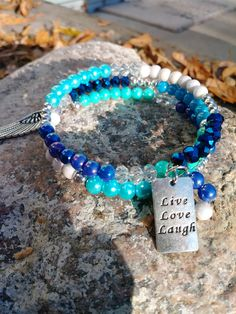 Blue White Silver memory wire bracelet with angel wing & Live Love Laugh charms by PurpleMoonJewelryCA on Etsy