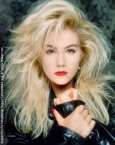big 90s hair, red lip, leather jacket, earrings... the recipe for every Glamour Shots shoot ever