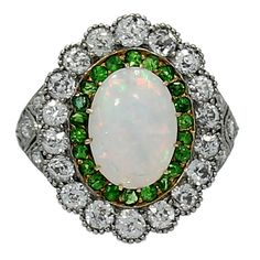Art Deco Platinum Opal and Diamond Ring. Platinum and yellow gold Art Deco ring with a Oval Opal (12.90 mm x9.70 mm), 23 Green Garnets and 24 Old Mine Cut Diamonds with approximately 2.00 carats