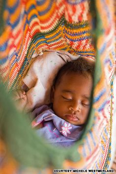 Papua New Guinea -- Baby sleeping in a Bilum (the woven string bag carry-all made by PNG women.