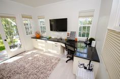 Clean, open, airy with built-in cabinets and a TV. Add a splash of color, and this room would make a perfect office.