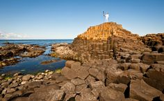 A torchbearer holds the Olympic flame aloft on the Giant's Causeway near Belfast, Northern Ireland, on June 4, Day 17 of the London 2012 Olympic Torch Relay