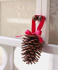 Dangle pinecones from every cabinet door: Form a 12-inch-long ribbon into a loop, and hot-glue to the pinecone's base. Tie another 12-inch-long ribbon into a bow, and hot-glue over the ends of the first ribbon.  - GoodHousekeeping.com