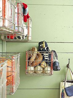 Corral the typical back-door clutter of an active family by screwing heavy-duty wire baskets into a mudroom wall. These old milk crates, which were purchased when an old dairy was closing, are great for holding sports equipment and winter accessories. The open baskets also allow dirt to fall through, making cleanup a cinch because vacuuming the floor is a lot quicker than cleaning individual bins.