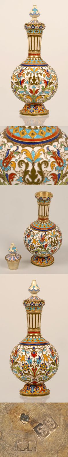 A Russian silver gilt and cloisonne enamel perfume flask, Feodor Ruckert, Moscow, circa 1890. The round bulbous body on a raised circular base with slightly flaring neck is decorated in multi-color floral enamel designs against an opaque white ground.