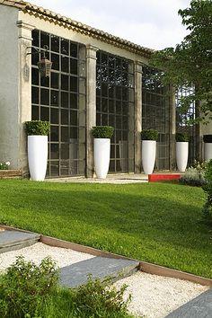 Gérard Faivre à Eygalières: Le Mas des Isords. Série de buis dans des grands vases blanc Ego.