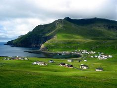 Village Fámjin. The village is located near the sea Fámjin in that part of the bay, where it is often plagued by huge waves, although it is partially protected by stone reef, which becomes visible at low tide. The village is surrounded by beautiful scenery and high mountains