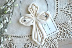 This salt dough Cross Ornament is simple and elegant! Unpainted, the natural, earthy color of the dough shines through. A hint of glitter wash is added for just a touch of shine. Ornament is imprinted on front, backs are smooth for writing, or just leave plain. I'm happy to add a name and year if you like. Perfect baptism or wedding ornament. Sealed with two coats of non-yellowing sealant so your ornament will last from year to year. Black wire hanger makes your cross easy to hang on your…