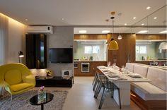 parede de cimento queimado e concreto aparente com amdeira e rack preto com tapete na sala e pendentes coloridos sobre a mesa de jantar