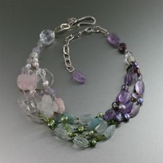 Aquamarine Beaded Gemstone Necklace  Evoke an ethereal essence with the beauty of raw gemstones with this stunning Aquamarine Beaded Gemstone Necklace. This 4-row tri-colored necklace creates a feminine aura with a rows of soft-hue Aquamarine, Amethyst, Rose Quartz, and Clear Quartz gemstone beads. The handmade fine silver chain closure adjusts from 18 to 22 inches.  This necklace provides elegance and sophistication with a twist of fun-loving charm.