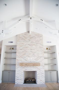Tumbled brick fireplace with grey bookshelves and arched beams by Rafterhouse.
