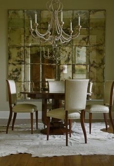 "Dining Room - ""The dining room epitomizes glamour. The table and chairs are both French, 1940s. The chairs are upholstered in a Pollack fabric. The antique mirrored screen in the background is vintage."