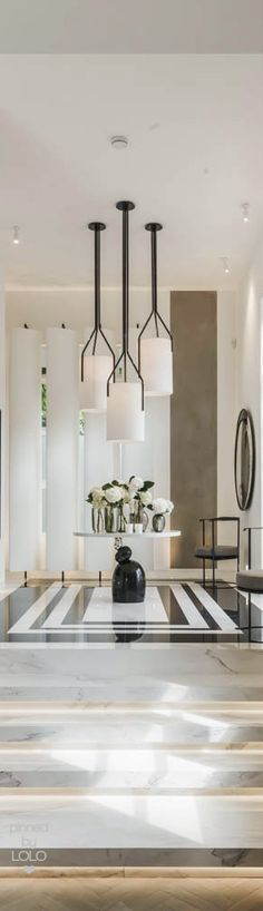 Luxury entryway | decor ideas with round tables and statement ceiling light  | www.bocadolobo.com #modernentryway #entrywayideas