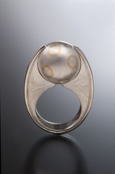WINGS OF MYSTERY by Michelangelo Stanchi  www.lalunadikala.com  22k gold circles inlayed into a fabricated sterling silver sphere hold it by a hand textured ring base. The ring was modeled in wax and casted in sterling silver. Limited edition.