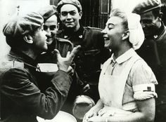 """Cuatro soldados de la """"División Azul"""" con uniforme alemán y boina roja hablan distendidamente con una enfermera de Cruz Roja en Grafenwöhr (Baviera - Alemania) en Julio de 1941."""