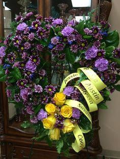 Personalized heart shaped standing easel spray of purple bi-color mums, lavender carnations, blue delphinium, yellow roses, lemon leaf, leather leaf, variegated pittosporum by Donna Jeffries