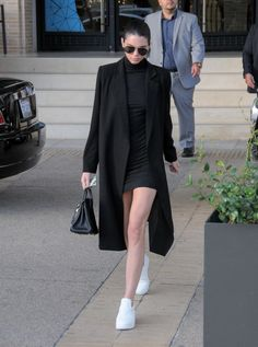 Kendall Jenner wears a black mini dress, black duster coat, and white slip-on sneakers at Barney's New York on Dec. 10, 2015 in Los Angeles, CA.