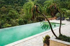 """Casa de campo Atibaia - """"Com a Mata Atlântica ao fundo, pedras mineiras revestem o piso ao redor da piscina de borda infinita, coberta de pastilhas da Vidrotil em diversos tons de verde."""" Projeto: João Armentano - Mais no Casa Vogue. (Foto: Ricardo Labougle)"""