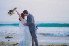 Bride and groom kissing by the ocean at their Wrightsville Beach, NC wedding.