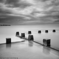 Coogee Beach, Sydney, NSW, Australia. Fine art black and white minimalist photography of the tidal pool at the Coogee Beach in Sydney, NSW, Australia with dramatic clouds.