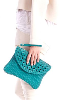 Teal woven clutch that can be worn three ways: As a wristlet, chain shoulder strap or simply carried.
