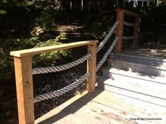 """Cedar post and top plate of this railing with 3"""" hawser rope sagging in between."""