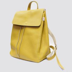 Our New simple Backpack/Rucksack. Front flap with magnetic catch, small pocket inside, adjustable shoulder straps and adjustable string to hold all your essentials together. Shown in beautiful soft yellow mustard coloured leather. The backpack is also available in: cerise, scarlet, lime, lavender, baby blue, black, chocolate, orange, forest green, navy, coffee, mushroom, khaki, purple and olive. Size 24 x 30 x 14cm.