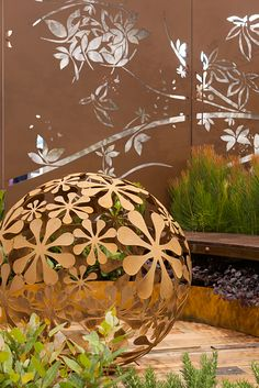 'Flower Ball' laser cut steel garden art by Entanglements, in a textural earthy rust finish. Behind - privacy screen 'Tropical birds', screen out the neighbours with decorative screening.