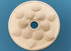 is a decorative plaster ceiling medallion that has a coastal theme. It contains Scallop shells on its surface and blends into any room with coastal or beach themed décor. It has a diameter and fits a canopy up to Coastal Living, Coastal Decor, Decorative Plaster, Hand Built Pottery, Scallop Shells, Ceiling Medallions, White Clay, Wall Decor, Ceramics