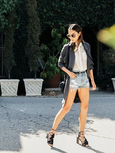 Jamie Chung wears a sheer button-down blouse, belted cutoffs, a gray trench, crossbody bag, and lace-up heels